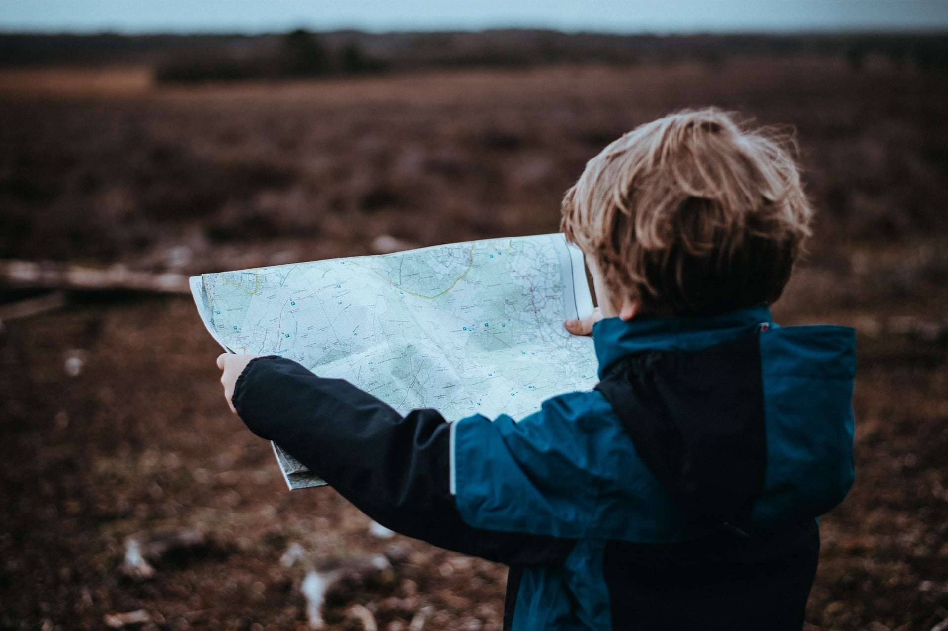 Child reading a map on a hike
