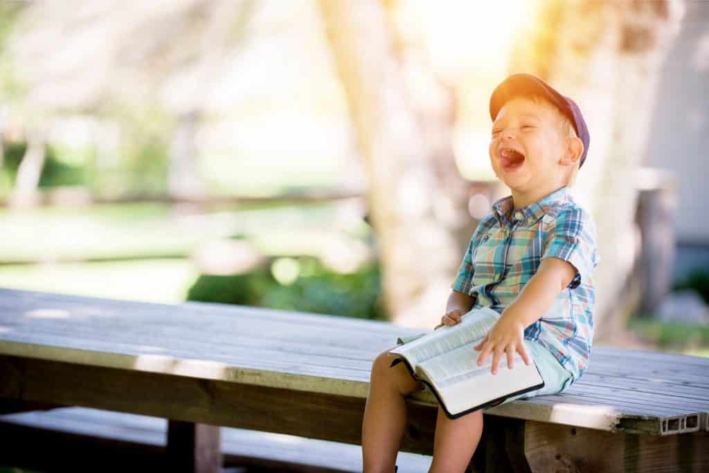 Boy laughing on a bench
