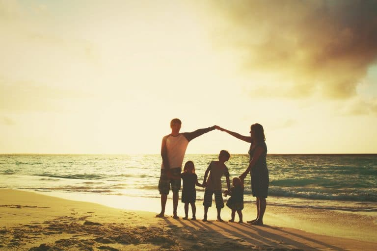Family Protection Happy family on a beach at sunset